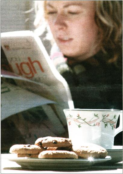 Photo of a woman taking tea while reading