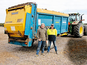 Two farmers stand before a tractor and trailer in a field.