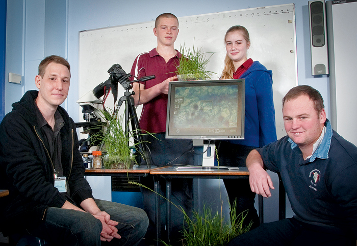 Image of two seated students and two standing students with research equipment and plants