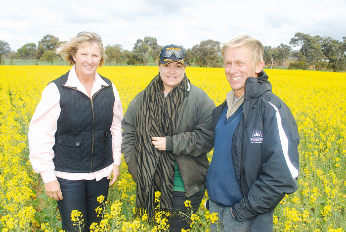 Three people pose in a field of canola