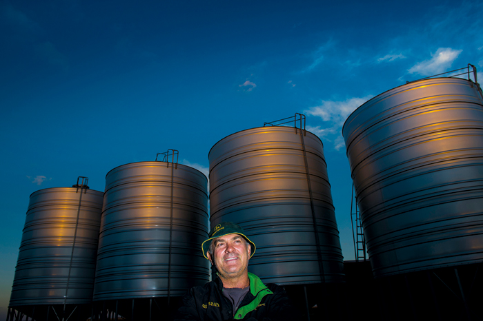 Man stands in front of silos