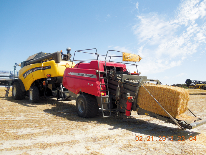 Image of a harvester towing a baler