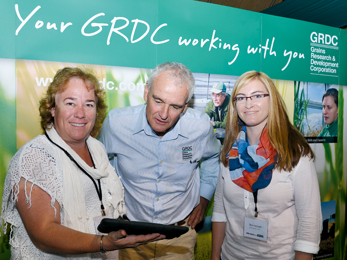 Photo of two women and a man in front of a GRDC poster