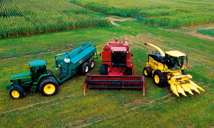 Photo of one green, one red and one yellow machine - arranged on a field