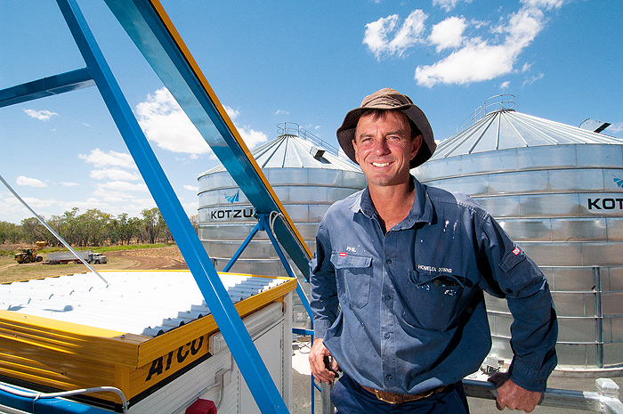 Image of a man standing in front of storage silos
