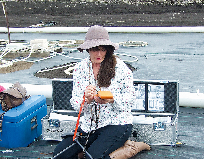 A woman with research equipment in the field