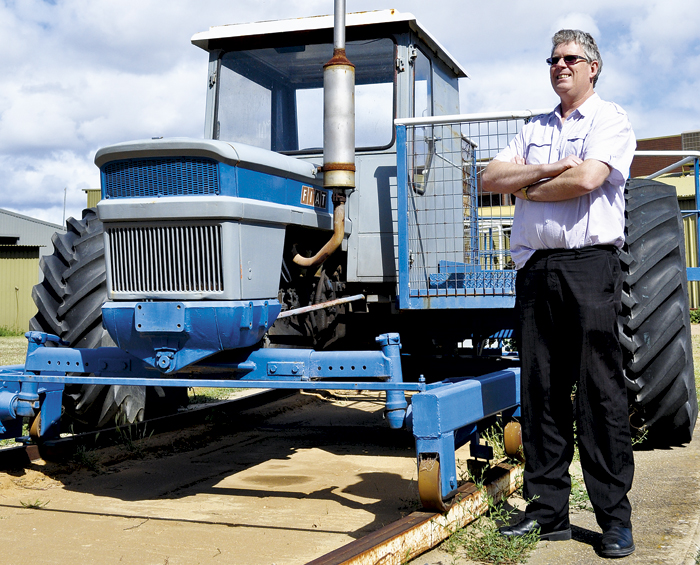 Photo of man standing by tractor