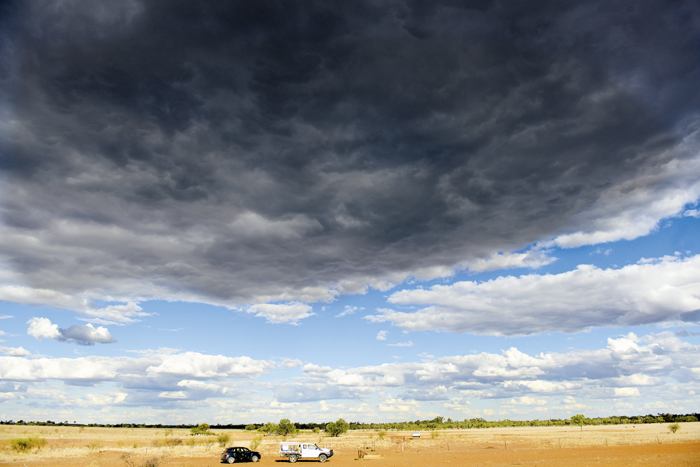Photo of two cars on sparse land and dark clouds