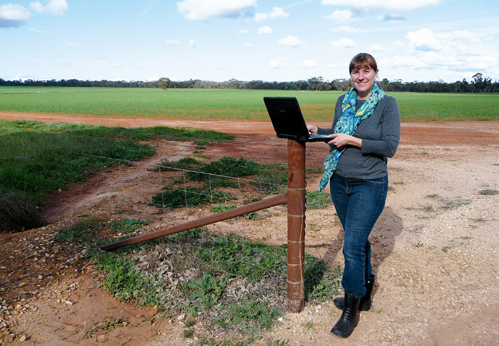 Image of a woman in a paddock with a laptop