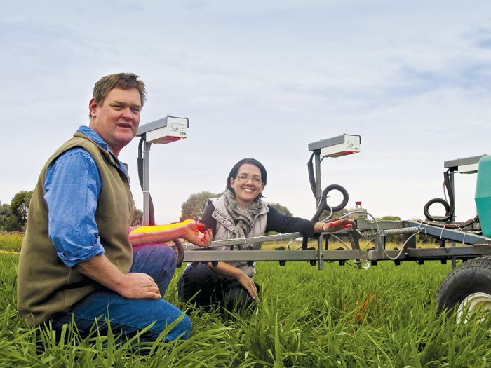 Photo of man and woman kneeling with machinery