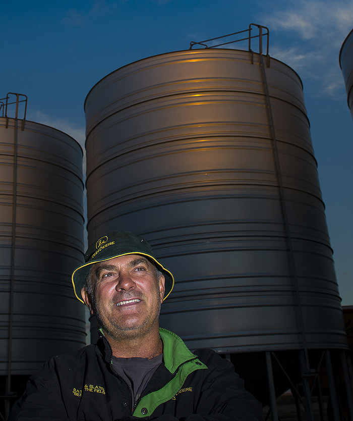 Photo of man in hat standing in front of a silo