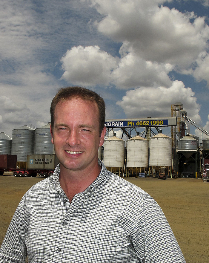 Photo of man smiling with silos behind