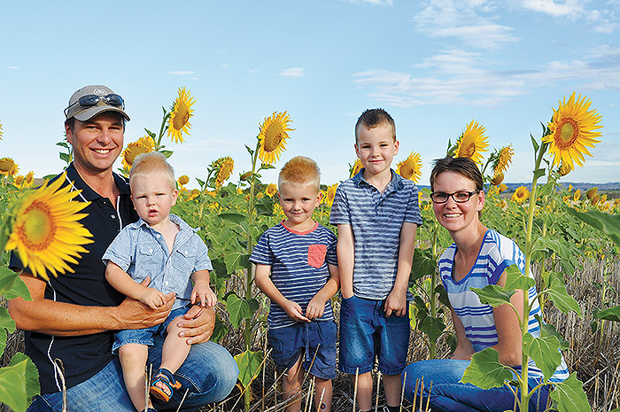 A family of 3 boys husband and wife sit in field of sunflowers facing the camera