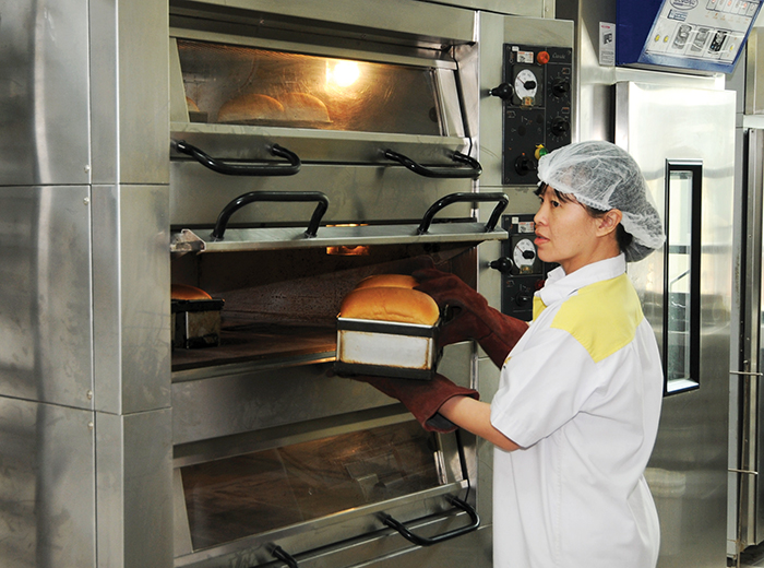 Woman putting bread into large oven