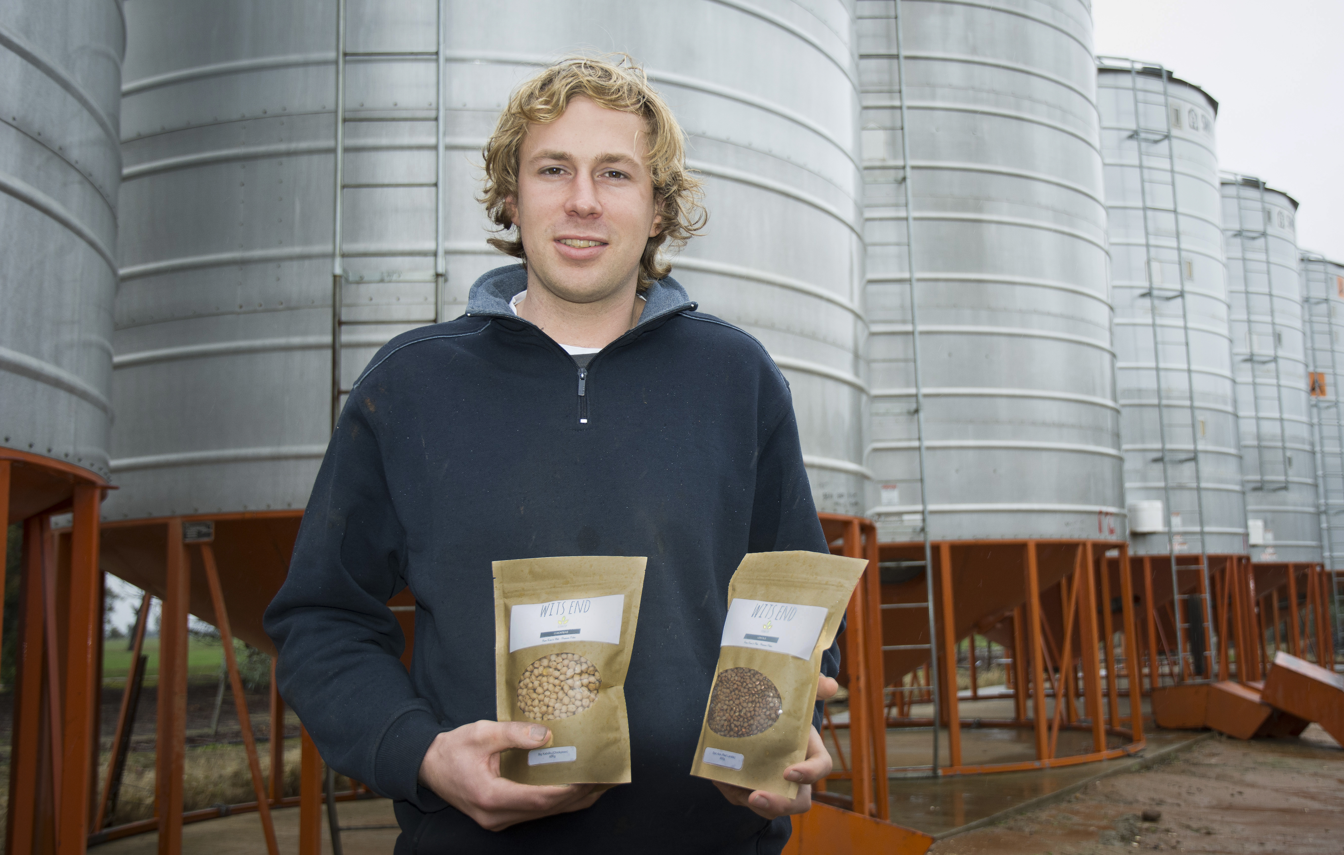 Photo of Scott Niewand, holding bags of his Wits End pulses
