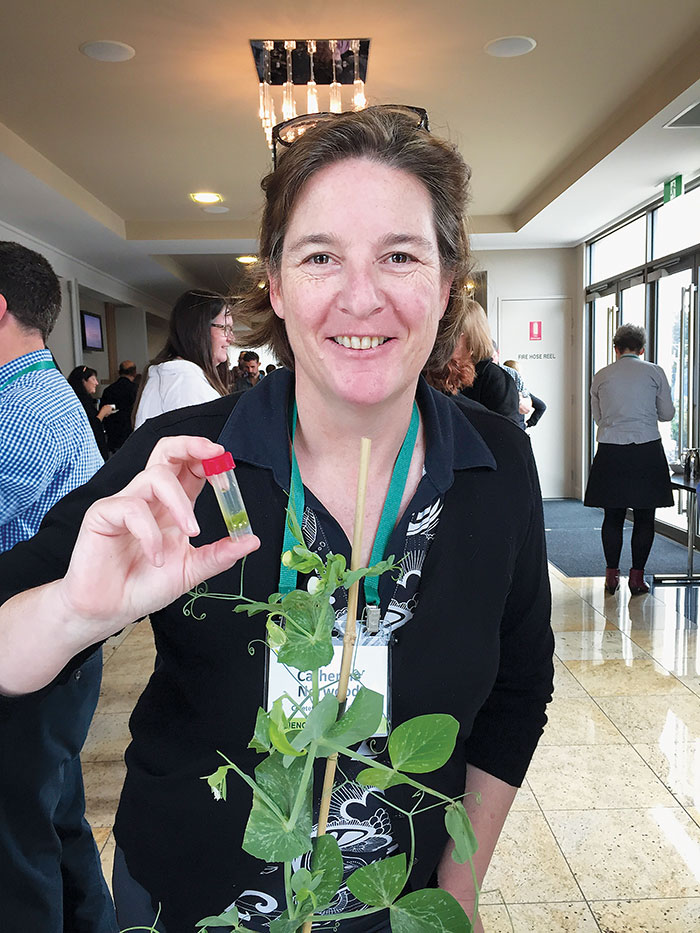 Photo of GroundCoverTM writer Catherine Norwood with a vial of infected leaf