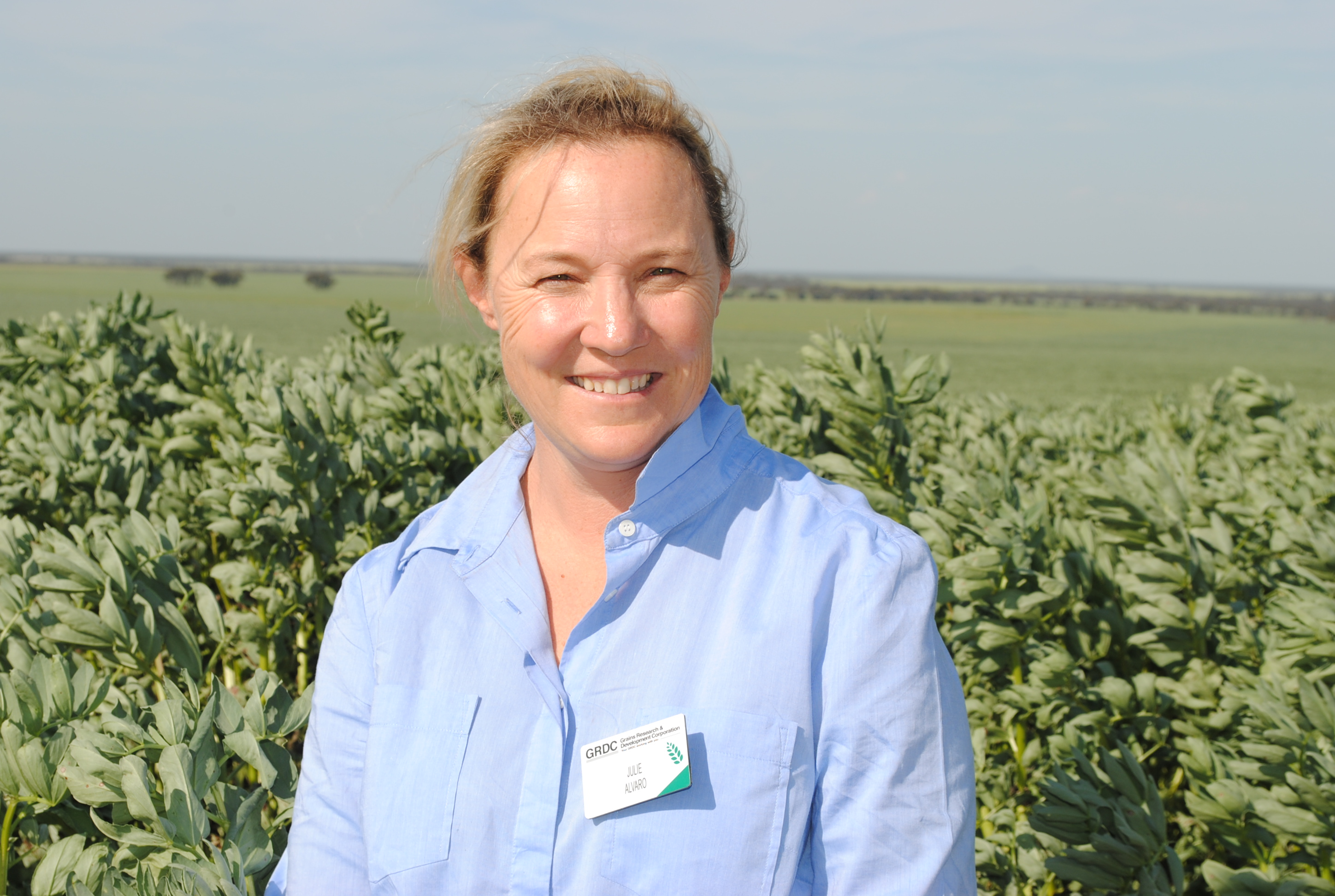 A woman standing in a field smiling, facing the camera.