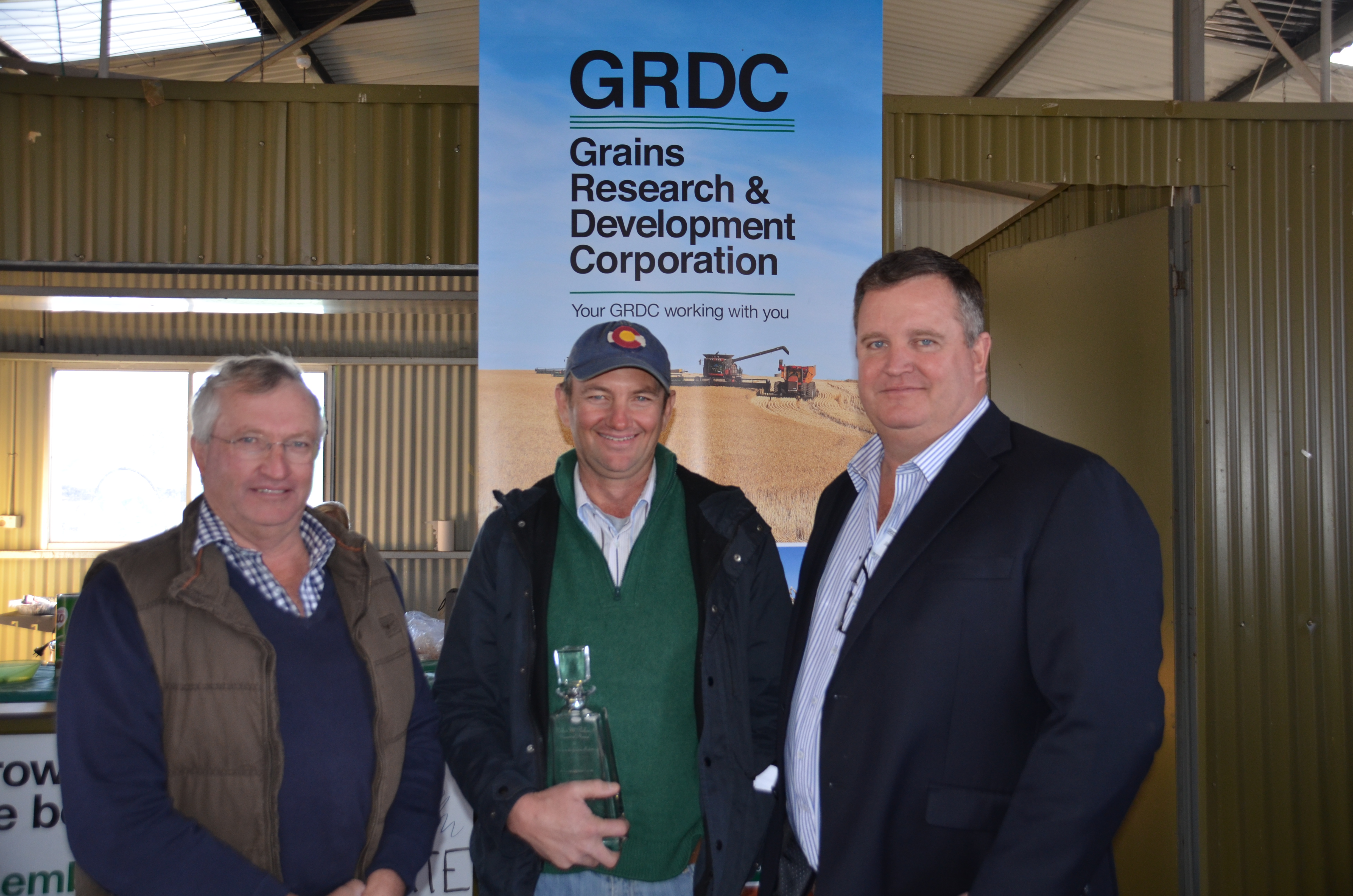 Image of GRDC northern panel chair James Clark presenting Spring Ridge farmers Gordon and David Brownhill with the Bruce McClelland Memorial Award.