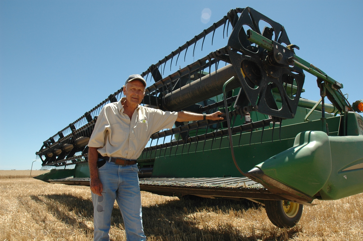 Dr Graeme Quick leans his left hand on a green harvester
