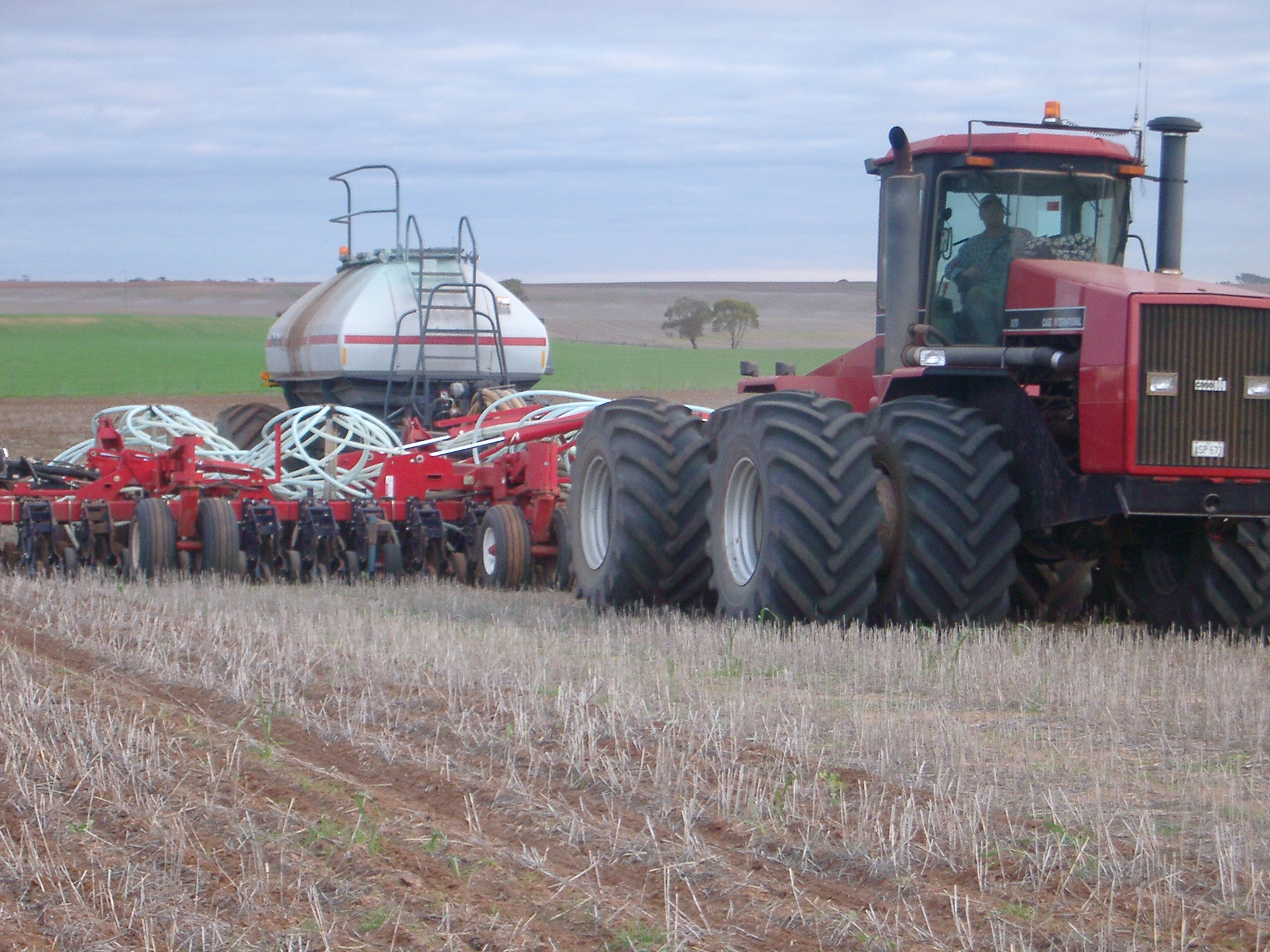 Tractor pulling a seeding rig.
