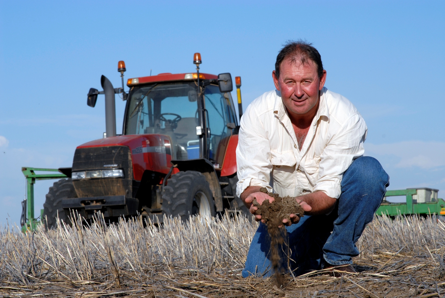 Keith Perrett kneeling in a harvested paddock with soil pouring through his hands. A red harvester can be seen in the background.