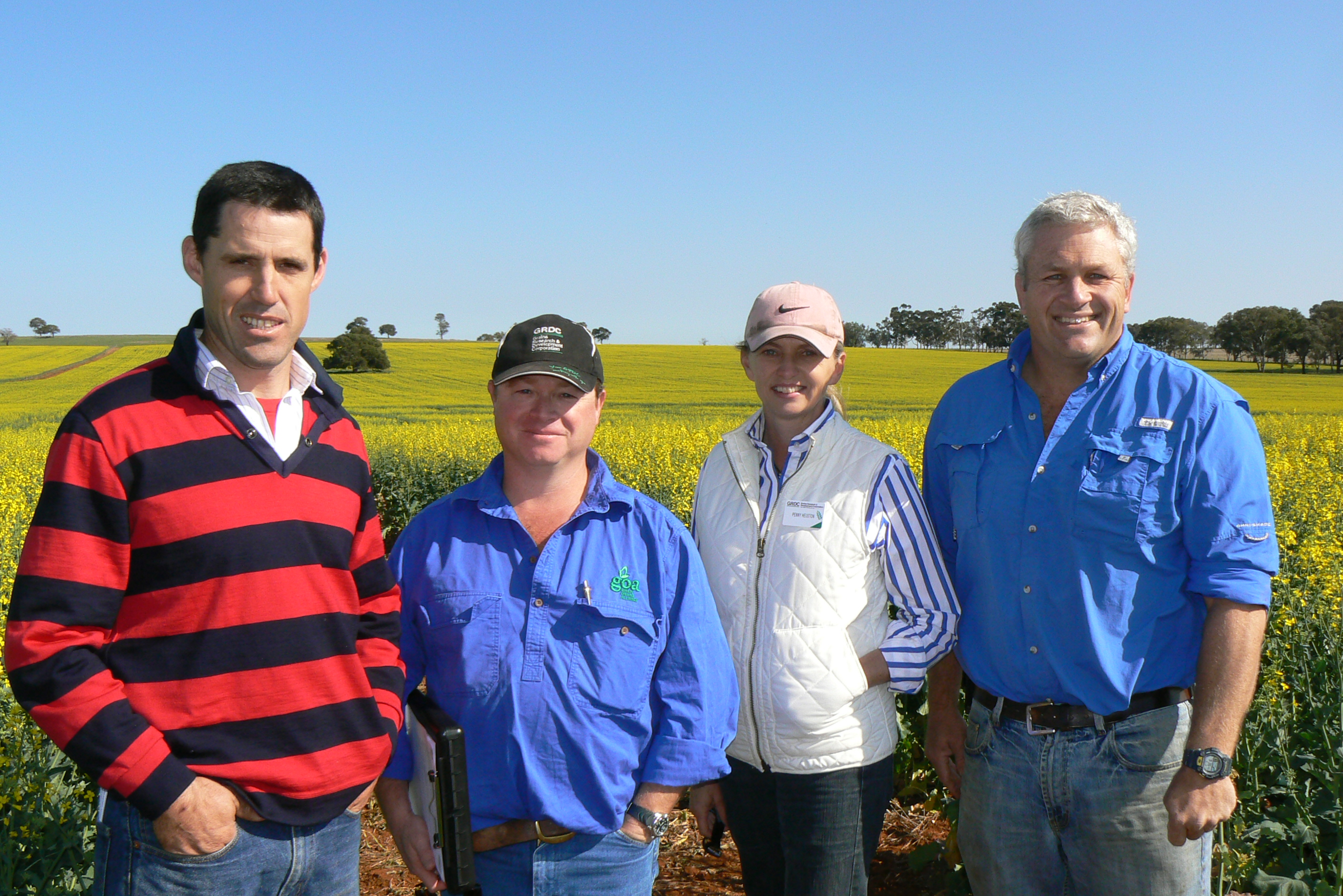 """Will Martel, Penny Heuston, Maurie Street and Joe Mason stand in front of a paddock of yellow canola at """"Spicer's Run"""" in Spicer's Creek, NSW."""