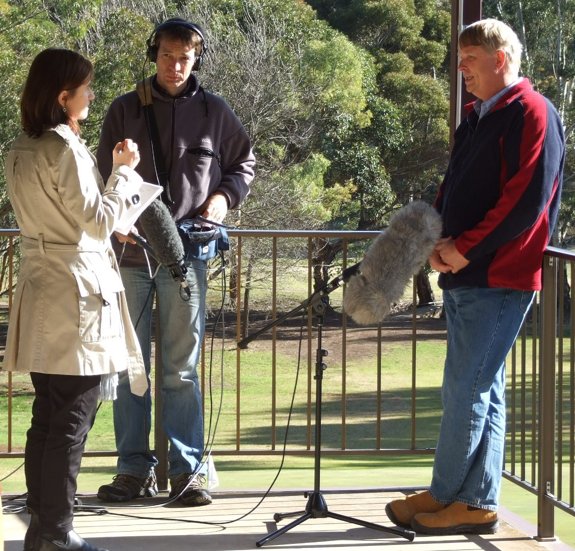 Prue Adams conducts an interview, with cameraman and recording equipment in frame.