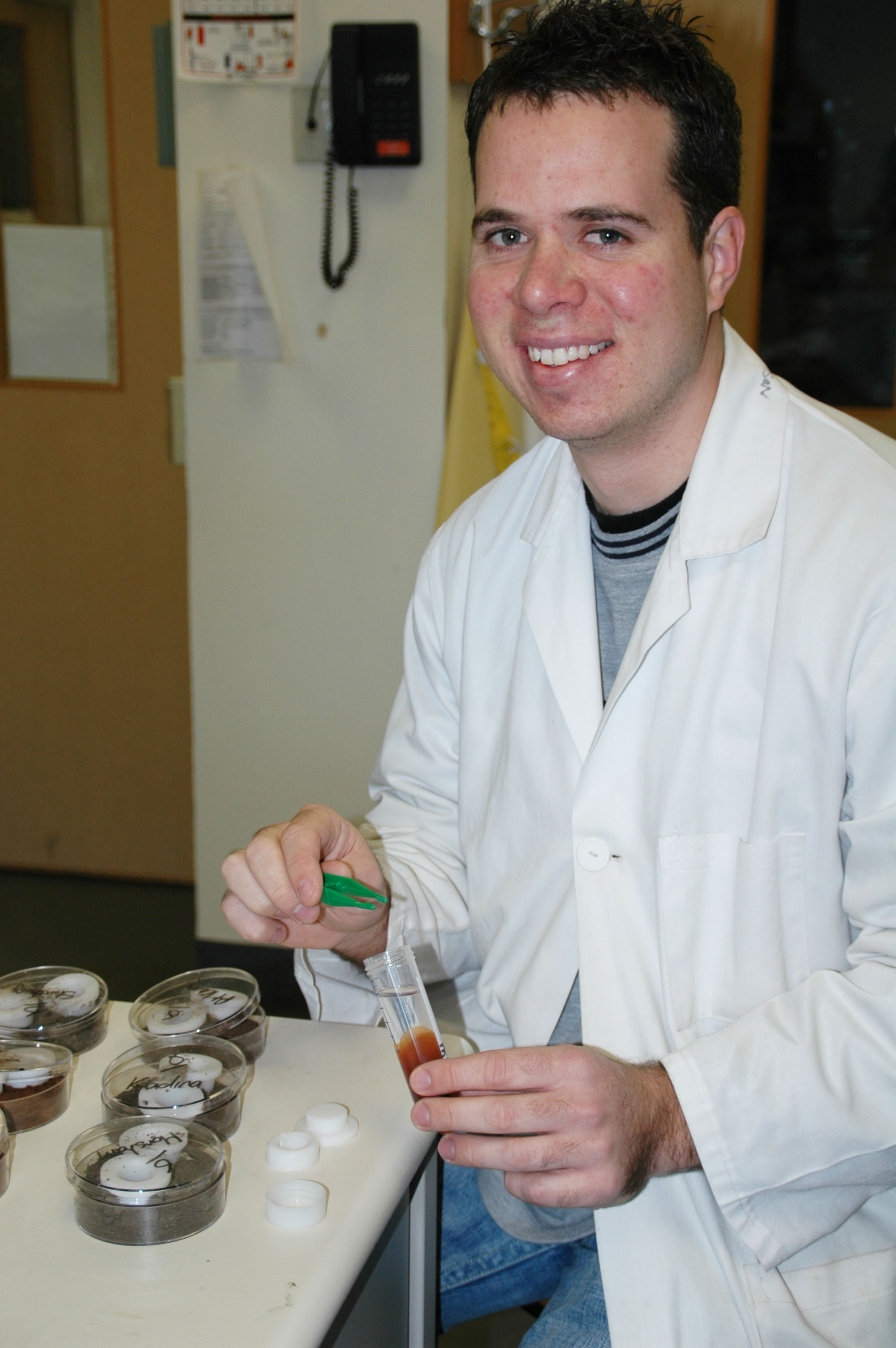 Dr Sean Mason, University of Adelaide, holding a test tube in his right hand and tweezers in his left hand.