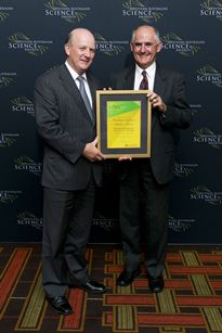 Stephen Powles and John Day standing next to each other holding award in a frame