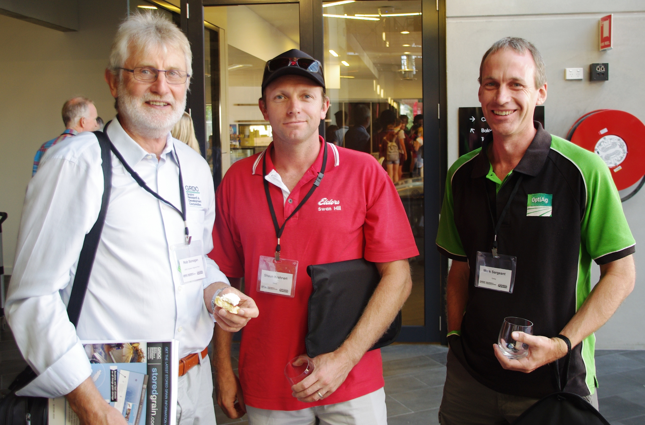 3 men smiling at the camera while present at a conference